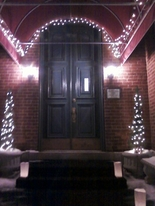 The Olde North Chapel entrance and night illuminated with white lights and luminaries
